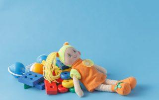 Doo laying on pile of toys with bright blue background