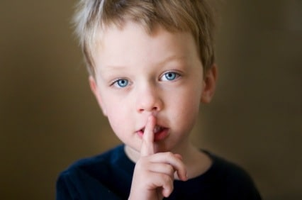 Little boy with finger up to lips in shush motion