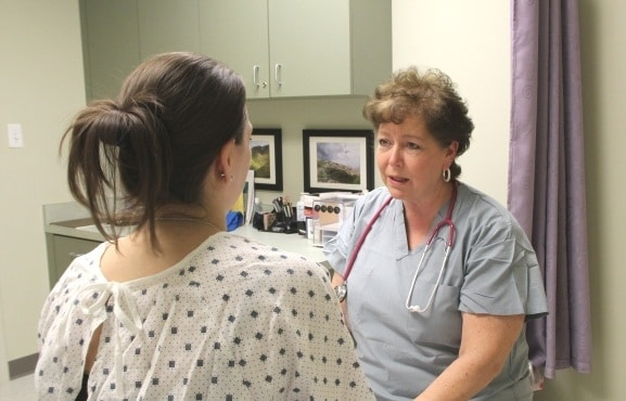 Compassionate nurse talking to female in hospital gown
